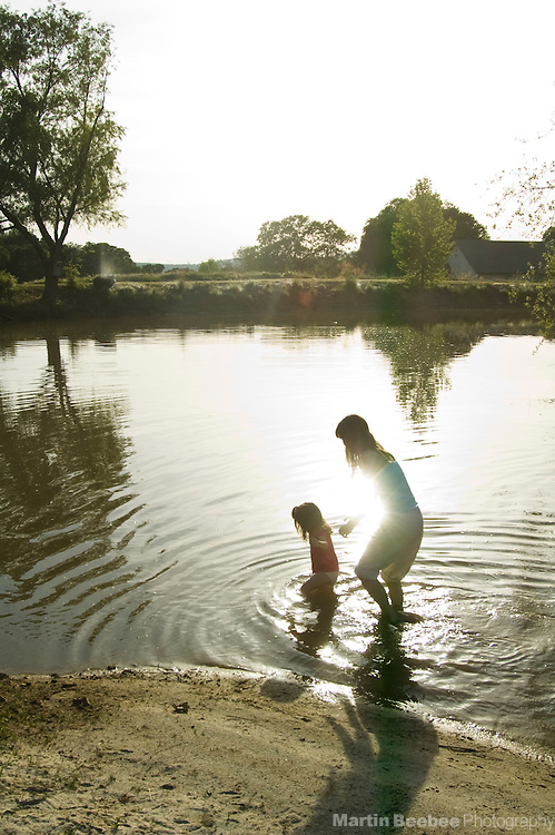 A woman watches over a toddler as they wade through a pond