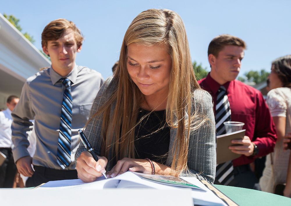 A College of Business freshman signs a book after Freshman Convocation outside of Nelson Commons, on Saturday, August 22, 2015. Photo by Kaitlin Owens
