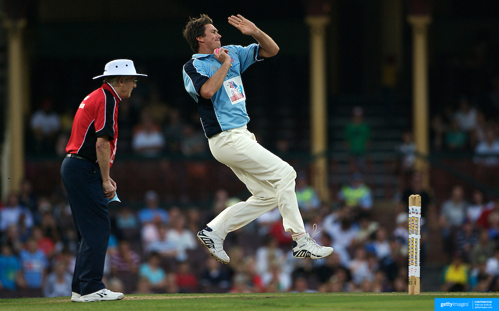Glenn McGrath bowling is watched by umpire Michael Parkinson during  Australia's Big Bash Cricket match to raise money for the Victorian Bushfire Appeal at the Sydney Cricket Ground, Sydney, Australia on February 22, 2009. The match was attended by over 20,000 spectators. Photo Tim Clayton
