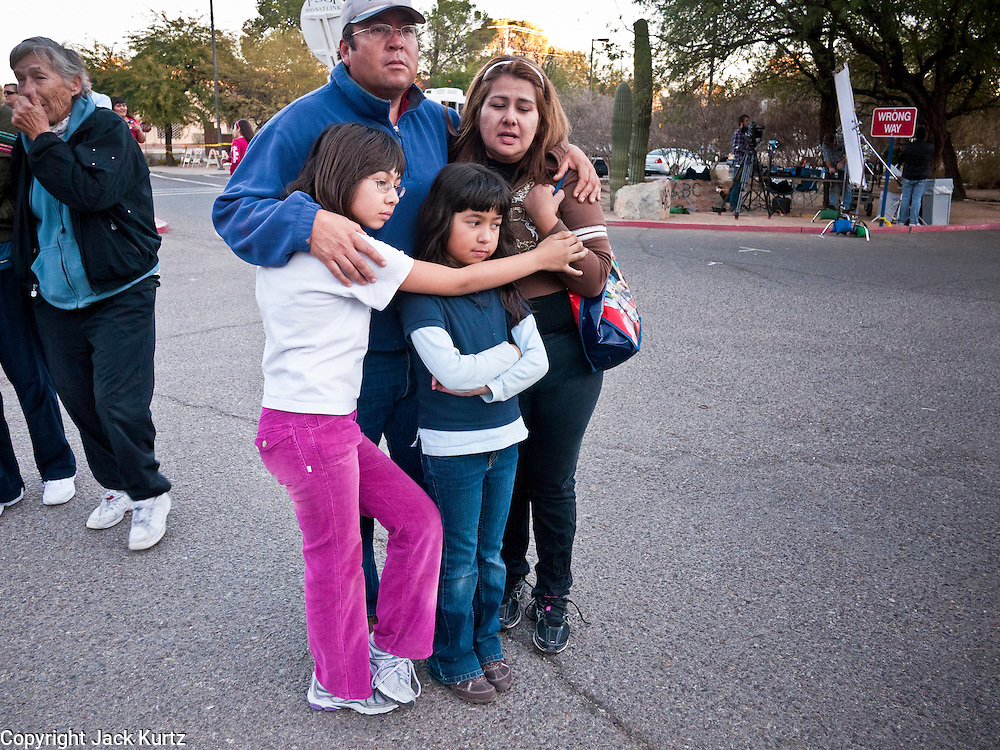"15 JANUARY 2011 - TUCSON, AZ: A family looks at the memorial on the lawn in front of the University Medical Center in Tucson, AZ, Saturday, January 15. The memorial has been growing since the mass shooting last week. Six people were killed and 14 injured in the shooting spree at a ""Congress on Your Corner"" event hosted by Congresswoman Gabrielle Giffords at a Safeway grocery store in north Tucson on January 8. Congresswoman Giffords, the intended target of the attack, was shot in the head and seriously injured in the attack. She is hospitalized at UMC. The alleged gunman, Jared Lee Loughner, was wrestled to the ground by bystanders when he stopped shooting to reload the Glock 19 semi-automatic pistol. Loughner is currently in federal custody at a medium security prison near Phoenix.  Photo by Jack Kurtz"