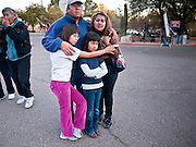 """15 JANUARY 2011 - TUCSON, AZ: A family looks at the memorial on the lawn in front of the University Medical Center in Tucson, AZ, Saturday, January 15. The memorial has been growing since the mass shooting last week. Six people were killed and 14 injured in the shooting spree at a """"Congress on Your Corner"""" event hosted by Congresswoman Gabrielle Giffords at a Safeway grocery store in north Tucson on January 8. Congresswoman Giffords, the intended target of the attack, was shot in the head and seriously injured in the attack. She is hospitalized at UMC. The alleged gunman, Jared Lee Loughner, was wrestled to the ground by bystanders when he stopped shooting to reload the Glock 19 semi-automatic pistol. Loughner is currently in federal custody at a medium security prison near Phoenix.  Photo by Jack Kurtz"""