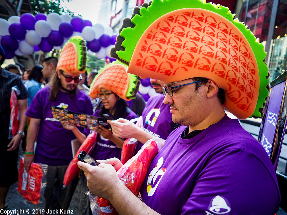 24 JANUARY 2019 - BANGKOK, THAILAND:  Americans look at the Taco Bell menu before the grand opening of the first Taco Bell in Thailand, which opened Thursday. People started lining up 14 hours before the restaurant opened. The restaurant has a 215 square meter space in the Mercury Ville, a mixed use retail/office building in central Bangkok. Taco Bell is owned by Yum Brands, which also owns KFC, Pizza Hut, and WingStreet. Taco Bell in Thailand joins KFC, which has more than 500 restaurants in Thailand and Pizza Hut, which recently started expanding in Thailand.   PHOTO BY JACK KURTZ