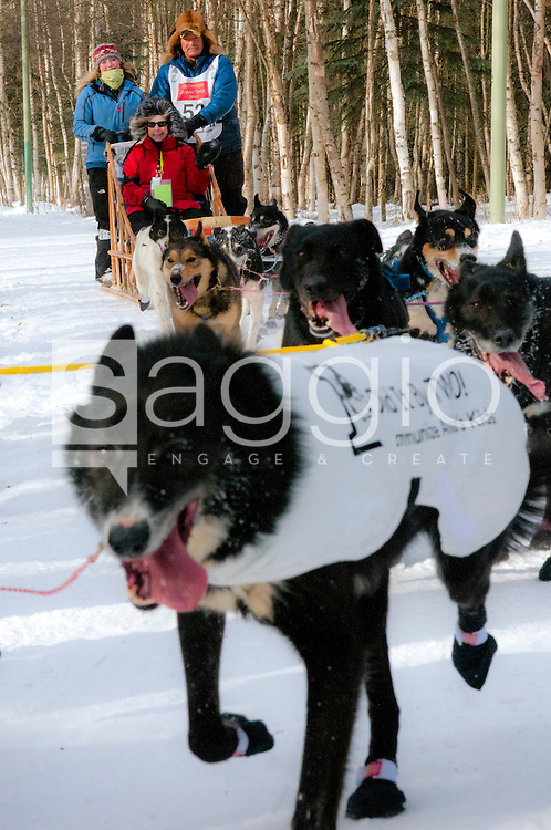 Musher Sonny Lindner and Iditarider Mary Arnn ride along the Chester Creek Trail during the 2011 Iditarod Ceremonial Start.