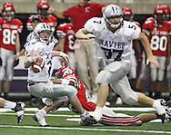 Xavier tailback Pat Chizek (23) can't hang onto the ball as he is hit by City High linebacker James Taylor (22) in their Class 4A semifinal game at the UNI Dome in Cedar Falls on Friday November 13, 2009. The ruling was Chizek was down before the ball came out.
