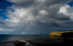 © Licensed to London News Pictures. 28/07/2012..Saltburn, England..Rain clouds and a rainbow form off the coastline as the sun lights up the cliffs at Saltburn in Cleveland..Photo credit : Ian Forsyth/LNP