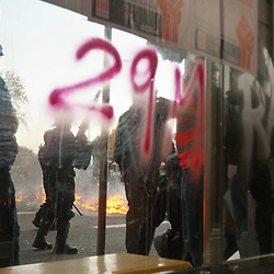 29M, representing the day of the strike, is painted on the glass of a bus stop while police confront rioters.