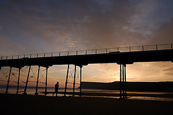 © Licensed to London News Pictures. <br /> 08/10/2014. <br /> <br /> Saltburn, United Kingdom<br /> <br /> A man walks under the pier at dawn on Saltburn beach in Cleveland.<br /> <br /> Photo credit : Ian Forsyth/LNP