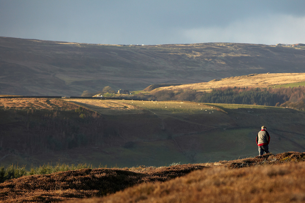 A photograph of a yorkshireman in a flat cap as he walks in the north york moors national park in England