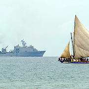 100119-N-5345W-110.BONEL, Haiti (Jan. 19, 2010).A sailboat laden with Haitians makes it's way across the calm waters off the coast of Bonel, Haiti, as the amphibious dock landing ship USS Carter Hall (LSD 50) operates in the distance. The multi-purpose amphibious assault ship USS Bataan (LHD 5) is on station in Haiti along with the amphibious dock landing ships USS Fort McHenry (LSD 43), USS Gunston Hall (LSD 44), and USS Carter Hall (LSD 50) as the Bataan Amphibious Relief Mission in support of Operation Unified Response, a joint operation providing military support capabilities to civil authorities to help stabilize and improve the situation in Haiti following a 7.0 magnitude earthquake that devastated the island nation. (U.S. Navy photo by Mass Communication Specialist 2nd Class Kristopher Wilson/Released)