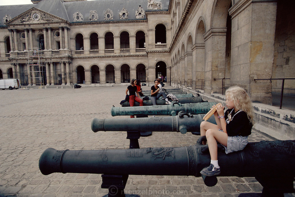Courtyard of Les Invalides. A young girl eats a baguette while sitting on a cannon. Paris, France.