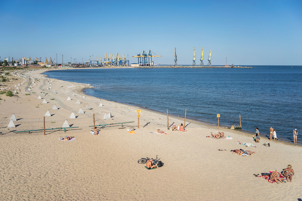 MARIUPOL, UKRAINE - AUGUST 30, 2015: People relax on Peschanka Beach, part of which has been fenced off and studded with tank traps and concertina wire to guard against an invasion from sea, in Mariupol, Ukraine. The beach is located on the western side of the city, away from the direction of the front lines. CREDIT: Brendan Hoffman for The New York Times