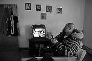 Carlos watches TV alone inhis room.  Carlos Raposa, 49, is dealing with diabetes.  Mr. Raposa has lost both legs below the knees to complications due to diabetes.  As his condition has worstened over the years Carlos has had greater difficulty dealing with his condition.  Increasingly, Carlos has fallen greater into depression and has turned to smoking and drinking to deal with it.  What used to be monthly visits to the hospital has turned into weekly excursions with ever longer stays in hospital.  Family members have become ever more worried about Carlos' drop in weight and his inability to move on his own any longer.  For someone who was an athletic figure, Carlos has become a shadow of his former self.