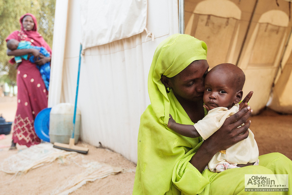 A woman holds her child as she sits outside a tent at a UNICEF-sponsored therapeutic feeding center at the Mongo hospital in the town of Mongo, Guera province, Chad on Tuesday October 16, 2012.