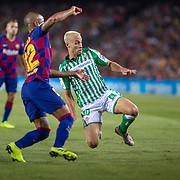 BARCELONA, SPAIN - August 25:  Rafinha #12 of Barcelona is tackled by Sergio Canales #10 of Real Betis during the Barcelona V  Real Betis, La Liga regular season match at  Estadio Camp Nou on August 25th 2019 in Barcelona, Spain. (Photo by Tim Clayton/Corbis via Getty Images)