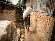 06 JUNE 2014 - IRRAWADDY DELTA,  AYEYARWADY REGION, MYANMAR: A worker carries a bag of rice to a warehouse in Pathein, the administrative center of the Irrawaddy Delta (or Ayeyarwady Delta) in Myanmar. The region is Myanmar's largest rice producer, so its infrastructure of road transportation has been greatly developed during the 1990s and 2000s. Two thirds of the total arable land is under rice cultivation with a yield of about 2,000-2,500 kg per hectare. FIshing and aquaculture are also important economically. Because of the number of rivers and canals that crisscross the Delta, steamship service is widely available.   PHOTO BY JACK KURTZ