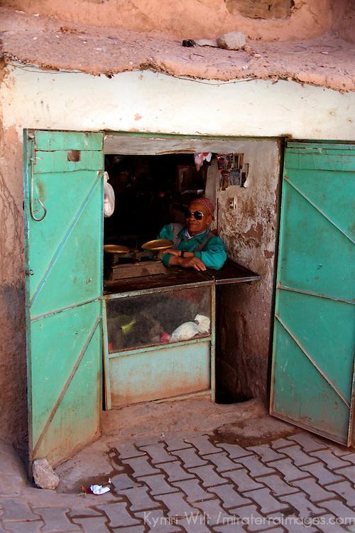 Africa, Morocco, Ouarzazate. Shop vendor relaxing in shade.