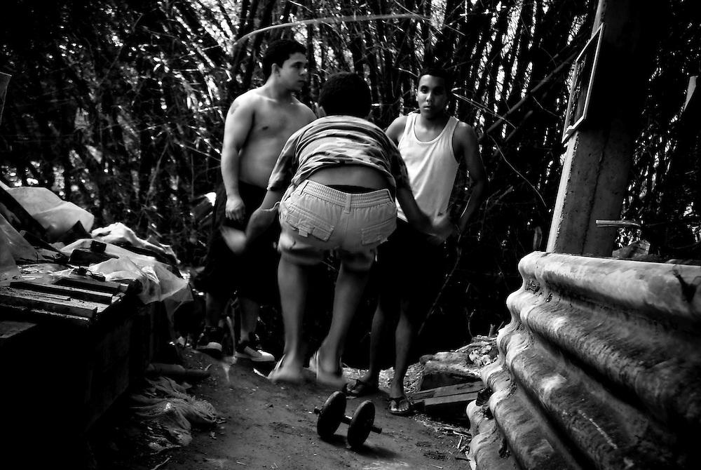 APUNTES SOBRE MI VIDA: LA PASTORA I - 2009/10<br /> Photography by Aaron Sosa<br /> Eigni, Mario Antonio y Andry, todos son miembros de la familia Montilla. Todas las tardes se reunen en el patio trasero de su casa para una jornada de ejercicios.<br /> La Pastora, Caracas - Venezuela 2009<br /> (Copyright © Aaron Sosa)
