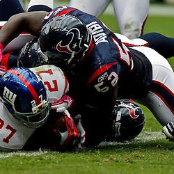 October 10, 2010; Houston, TX USA; New York Giants running back Brandon Jacobs (27) breaks the plane of the goal for a touchdown past Houston Texans linebacker Xavier Adibi (52) during the first half at Reliant Stadium. Mandatory Credit: Derick E. Hingle