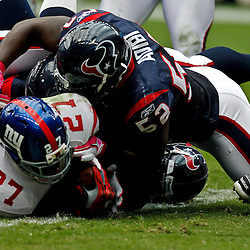 October 10, 2010; Houston, TX USA; New York Giants running back Brandon Jacobs (27) breaks the plane of the goal for a touchdown past Houston Texans linebacker Xavier Adibi (52) during the first half at Reliant Stadium. Mandatory Credit: Derick E. Hingle