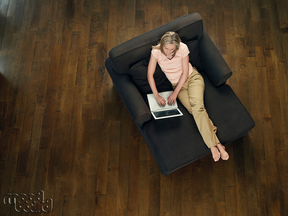 Mid-adult woman sitting on sofa using laptop view from above