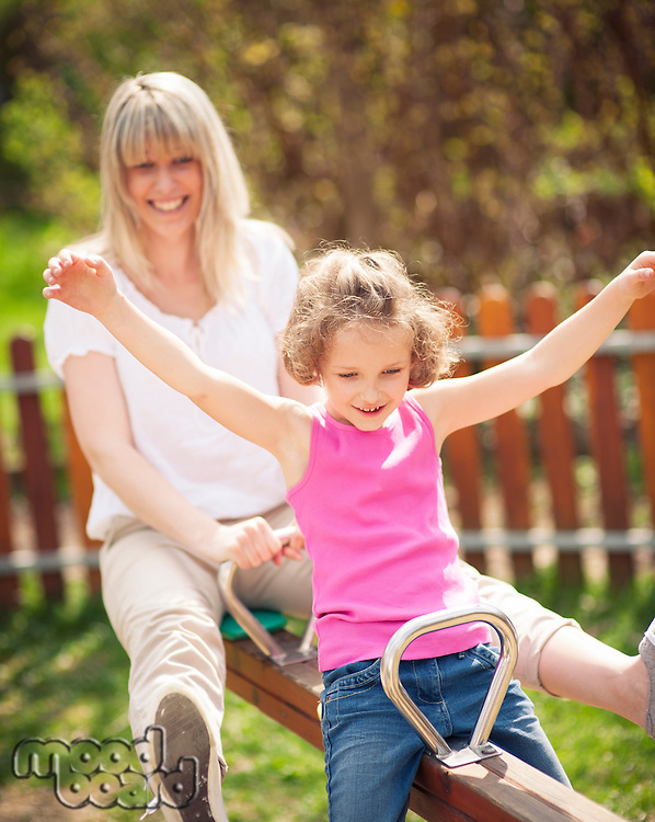 Mother and daughter ride seesaw together