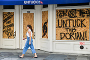 Charleston, South Carolina, USA. 03 September 2019. A young woman walks past a boarded up shop on King Street in the historic downtown in preparation for Hurricane Dorian September 3, 2019 in Charleston, South Carolina. The slow moving monster storm devastated the Bahamas and is expected to reach Charleston as a Category 2 by Thursday morning.