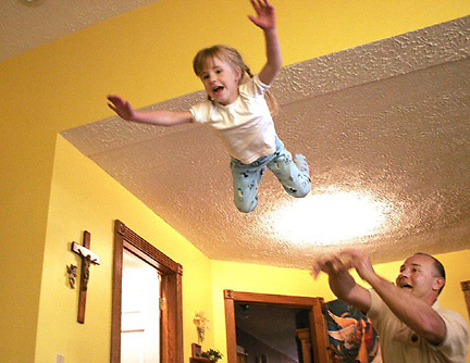 Girl flying through the air, lands on bed.
