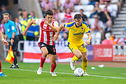 Callum Reilly (#33) of AFC Wimbledon takes on Luke O'Nien (#13) of Sunderland AFC of Sunderland AFC during the EFL Sky Bet League 1 match between Sunderland and AFC Wimbledon at the Stadium Of Light, Sunderland, England on 24 August 2019.