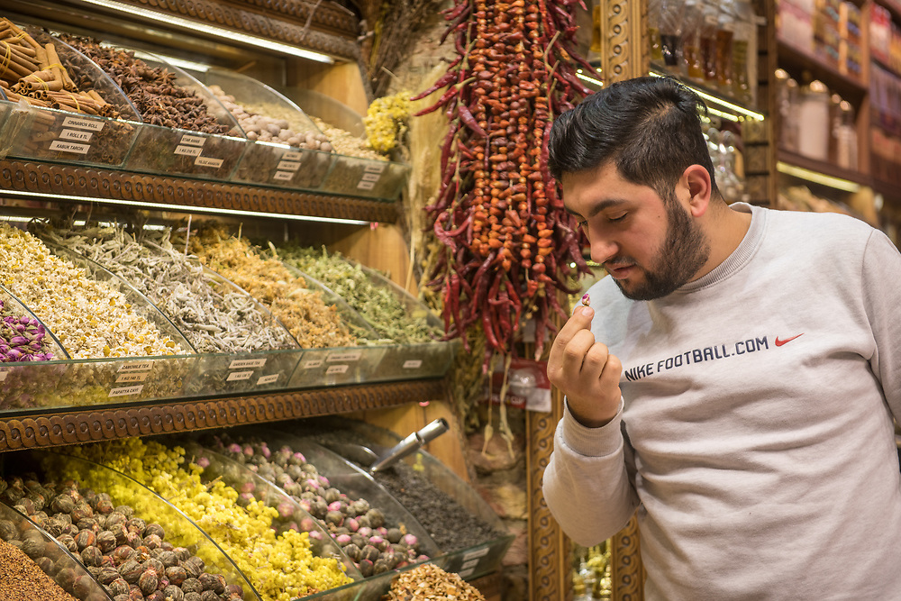 Adult male merchant carefully inspects flower tea in spice shop in Istanbul Spice bazaar in Turkey