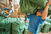 13 MARCH 2013 - ALONG HIGHWAY 13, LAOS: Lao warehouse workers move freight onto Lao trucks for shipment into markets in Laos near the end of Highway 13 in the Boten Special Economic Zone. The SEZ is in Laos immediately south of the Lao Chinese border. It has turned into a Chinese enclave but many of the businesses struggle because their goods are too expensive for local Lao to purchase. Some of the hotels and casinos in the area have been forced to close by the Chinese government after reports of rigged games. The paving of Highway 13 from Vientiane to near the Chinese border has changed the way of life in rural Laos. Villagers near Luang Prabang used to have to take unreliable boats that took three hours round trip to get from the homes to the tourist center of Luang Prabang, now they take a 40 minute round trip bus ride. North of Luang Prabang, paving the highway has been an opportunity for China to use Laos as a transshipping point. Chinese merchandise now goes through Laos to Thailand where it's put on Thai trains and taken to the deep water port east of Bangkok. The Chinese have also expanded their economic empire into Laos. Chinese hotels and businesses are common in northern Laos and in some cities, like Oudomxay, are now up to 40% percent. As the roads are paved, more people move away from their traditional homes in the mountains of Laos and crowd the side of the road living off tourists' and truck drivers.    PHOTO BY JACK KURTZ
