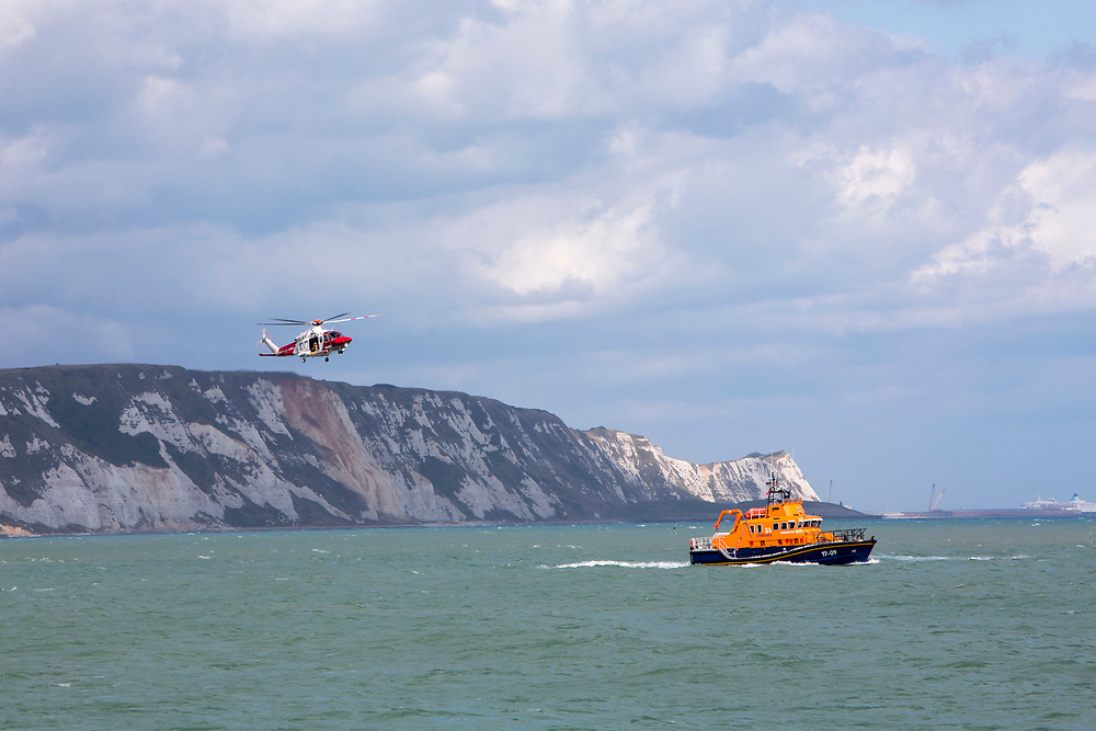 The HM Coastguard rescue helicopter (G-C1JW)  flying in front of the White Cliffs as it attempts to land a crew member on the back of the Royal National Lifeboat Institution RNLI Dover Life boat (17-09) during a training exercise in the sea just outside Folkestone Harbour, Folkestone, Kent. UK.(photo by Andrew Aitchison / In pictures via Getty Images)