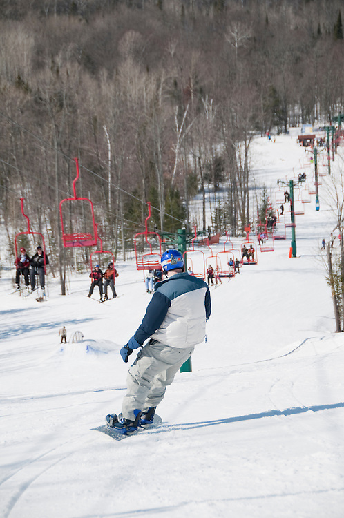 Skiers and snowboarders in the terrain park at Indianhead Mountain ski resort near Wakefield Michigan.