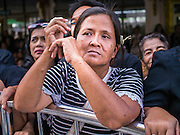 19 OCTOBER 2014 - BANG BUA THONG, NONTHABURI, THAILAND:  A woman watches Apiwan Wiriyachai's cremation at Wat Bang Phai in Bang Bua Thong, a Bangkok suburb, Sunday. Apiwan was a prominent Red Shirt leader. He was member of the Pheu Thai Party of former Prime Minister Yingluck Shinawatra, and a member of the Thai parliament and served as Yingluck's Deputy Prime Minister. The military government that deposed the elected government in May, 2014, charged Apiwan with Lese Majeste for allegedly insulting the Thai Monarchy. Rather than face the charges, Apiwan fled Thailand to the Philippines. He died of a lung infection in the Philippines on Oct. 6. The military government gave his family permission to bring him back to Thailand for the funeral. His cremation was the largest Red Shirt gathering since the coup.    PHOTO BY JACK KURTZ