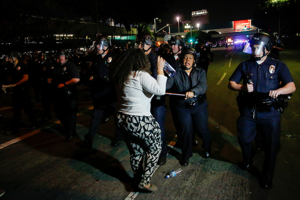 An LAPD officer uses her baton to push back a woman on Pico Blvd underneath the 110 Freeway. People protest the decision of the Ferguson grand jury and the death of Michael Brown on early morning Tuesday, November 25, 2014 in Los Angeles, Calif. (Patrick T. Fallon/ For the Los Angeles Times)