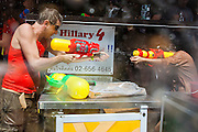 14 APRIL 2013 - BANGKOK, THAILAND:  A tourist shoots a water gun at a woman tending bar on Soi Nana on April 14, 2013 in Bangkok, Thailand. The Songkran festival is celebrated in Thailand as the traditional New Year's Day from 13 to 15 April. The throwing of water originated as a way to pay respect to people and is meant as a symbol of washing all of the bad away. PHOTO BY JACK KURTZ
