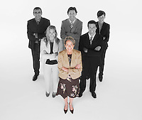 Ambitious businesswoman with team of professionals against white background