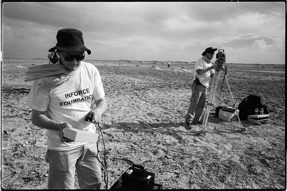 "Members of Inforce, a UK team of ""grave hunters"", set up the GPS/laser surveying system, preparing to scan the soil for disturbance to check for the presence of a mass grave, near Al-Musayab, Iraq. This was the first time the ensemble of high-tech geological tools had been employed to look for a mass grave."