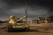 Under a veil of black smoke from the nearby burning oil wells, an Iraqi Army tank and a coalition helicopter are seen on the outskirts of Qayyarah, south of Mosul, on December 7, 2016.