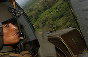 Colombian government coca verification flight from Tumaco airfield east into the jungle of Nari&ntilde;o. Crew chief signals that here there are two coca fields.<br />Flying in a Colombian army Blackhawk helicopter, with an escort of three Huey helicopter gunships. Using GPS devices, Colombian authorities verify the presence of coca farms deep in the leftist-guerilla FARC-held jungle.<br />In each area visited extensive coca cultivation was found. This is 'hot' mission needing to fly low for visual verification. On the previous day the helicopter was hit twice by FARC ground-fire.
