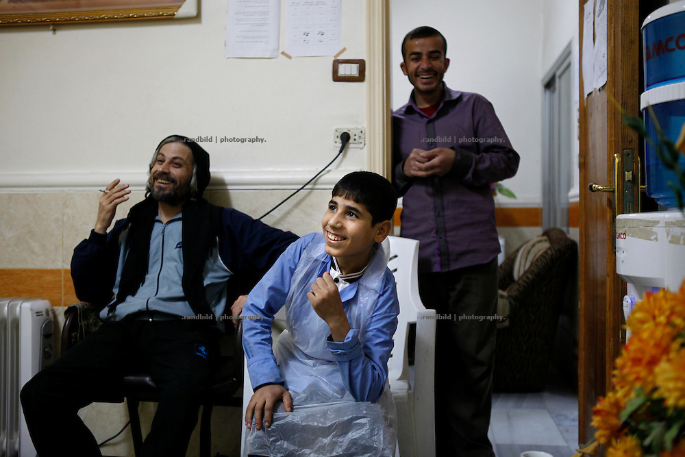 Teenager Wissam (real name withheld) at his work in Al-Noor Hospital in central Deir az-Zor. It´s been the largest hospital in town to treat injured or register deads from fightings or shelling in the embattled town at the banks of Eurphrates river. Conditions are poor and all staff works since two years almost non-stop. Even skilled teenager are needed to maintain proceedings as Wissam fullfills his job for his age in an incredible manner. Residents of eastern syrian town Deir az-Zor joined arab spring protests against the regime of Bashar al-Assad from its early beginning in March 2011. Since summer 2012 the town with few hundred thousand inhabitants is embattled between the Syrian Army and different opposing rebel groups like Free Syrian Army and Jabhat al-Nusra. Deir az-Zor is target to constant shelling by artillery, war planes and short range missiles. Almost 70 percent of the town is rebel held while government forces remain in control over some residental areas and a strategic important airport. Deir az-Zor is widely damaged and some areas almost totally destroyed by fierce and long lasting battles. All direct road connections to Deir az-Zor are cut and fighters and returning residents as well depend on one provisional supply line across the Euphrates river which is regularly targeted by government snipers.