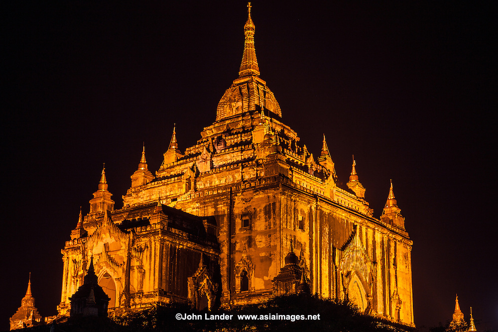 """Towering above the other monuments of Bagan, the magnificence in white which is the Thatbyinnyu takes its name from the Omniscience of the Buddha. Thatbyinnyutanyan in Myanmar language, Sabbannutanana in Pali, omniscience is given further explanation in contemporary inscriptions as """"knowing thoroughly and seeing widely.""""  Three receding terraces rise above each storey, ornamented with crenellated parapets and corner stupas. Above the terraces of the upper storey rises a curvilinear spire, surmounted by a slim, tapering stupa which takes the temple up to a height of 201 feet. The great height of the temple and the vertical lines of the ornamental features-the plain pilasters, the flame-like arch pediments, the corner stupas-give a soaring effect to the Thatbyinnyu..."""