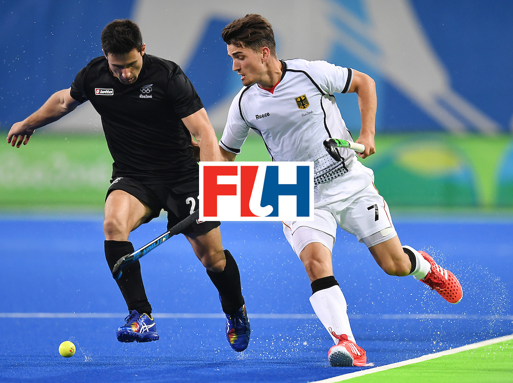 New Zealand's Kane Russell (L) vies with Germany's Moritz Trompertz during the men's quarterfinal field hockey Germany vs New Zealand match of the Rio 2016 Olympics Games at the Olympic Hockey Centre in Rio de Janeiro on August 14, 2016. / AFP / MANAN VATSYAYANA        (Photo credit should read MANAN VATSYAYANA/AFP/Getty Images)
