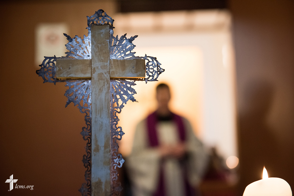 A cross frames the Rev. Dr. Gottfried Martens as he waits for visitors to arrive for worship on Sunday, Nov. 15, 2015, at the Dreieinigkeits-Gemeinde, a SELK Lutheran church in Berlin-Steglitz, Germany.  LCMS Communications/Erik M. Lunsford