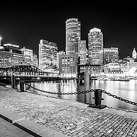 Boston skyline harbor at night black and white photo. Includes downtown Boston skyscrapers, Nothern Avenue Bridge, and Harborwalk cobblestone walkway.