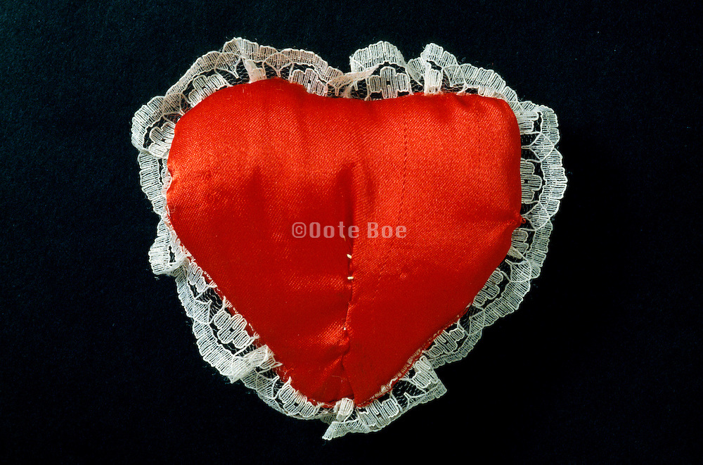 repaired heart cushion on black background