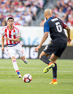 Miguel Almiron of Paraguay approaches to cover U.S. defender John Brooks during the first half of a Copa America Centenario group stage matchup at Lincoln Financial Field in Philadelphia on Saturday June 11, 2016. The U.S. defeated Paraguay 1-0.