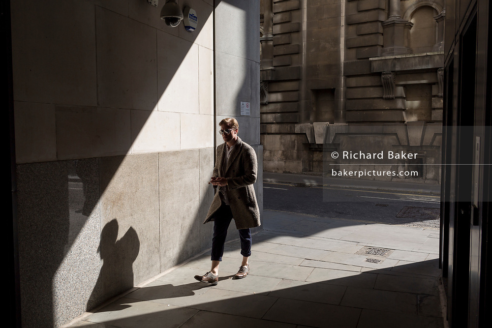A stylish man walks through shafts of light on Lombard Street in the heart of the capital's financial district, on 19th April, in the City of London, England.