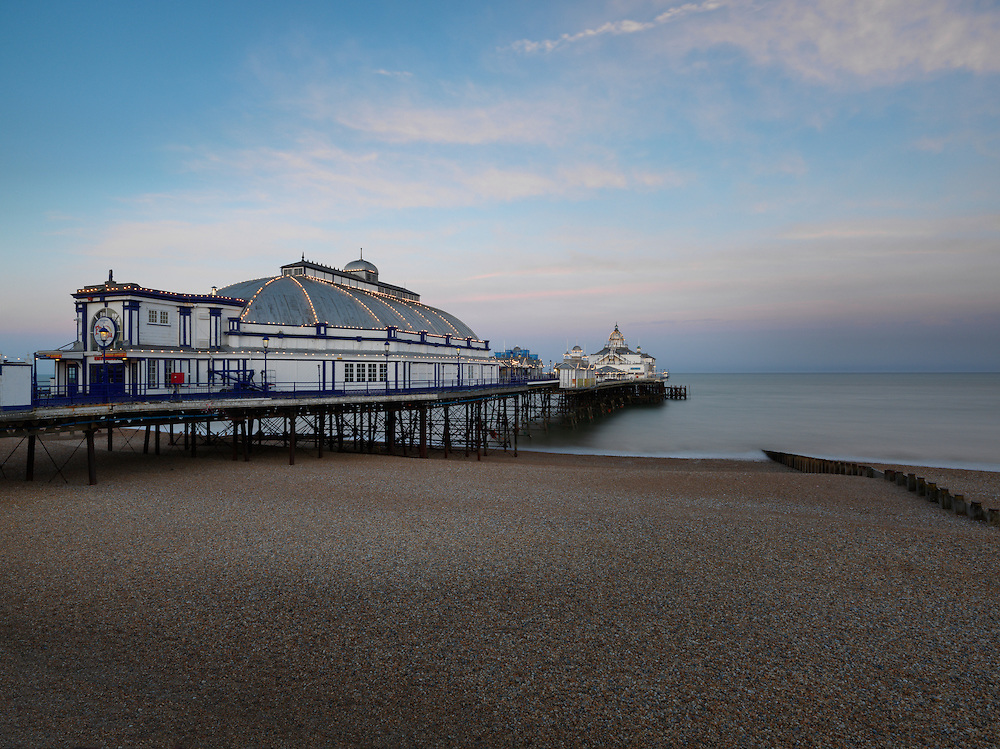 Old Victorian Amusement Pier on the English coast at Eastbourne lights up at dusk