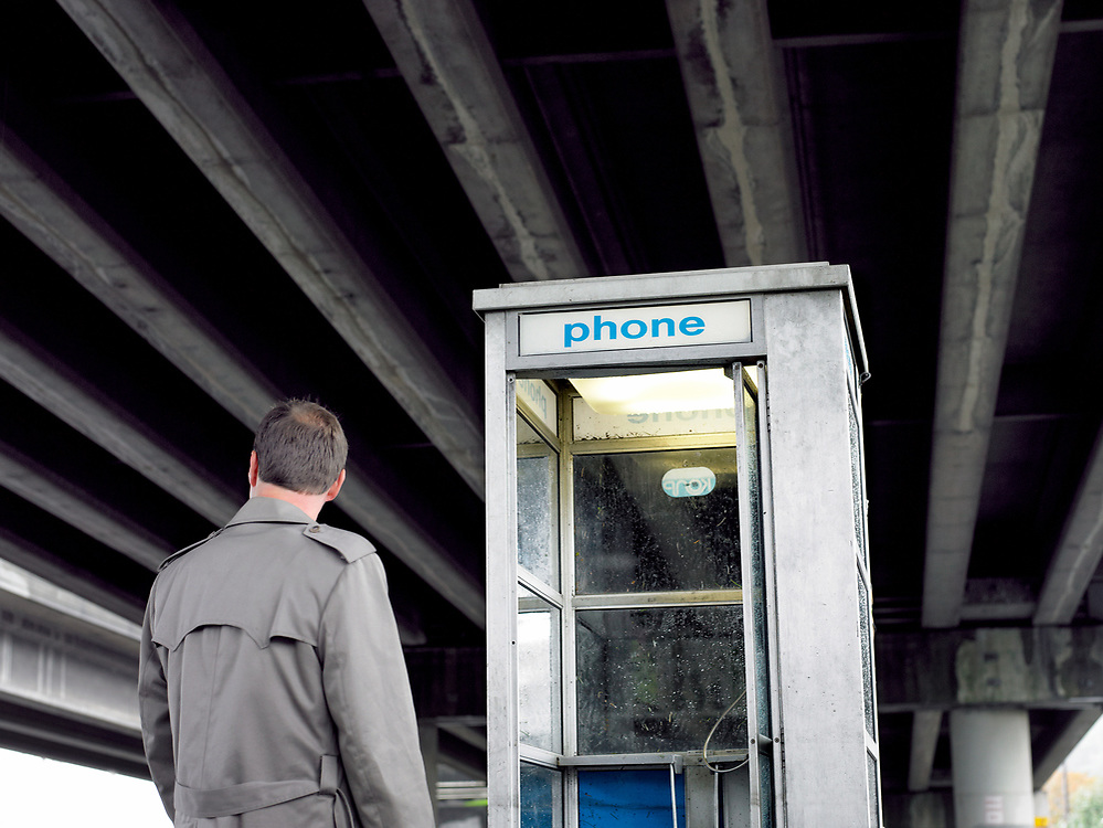 50's something man standing next to a pay phone booth, rear view under a freeway bridge.