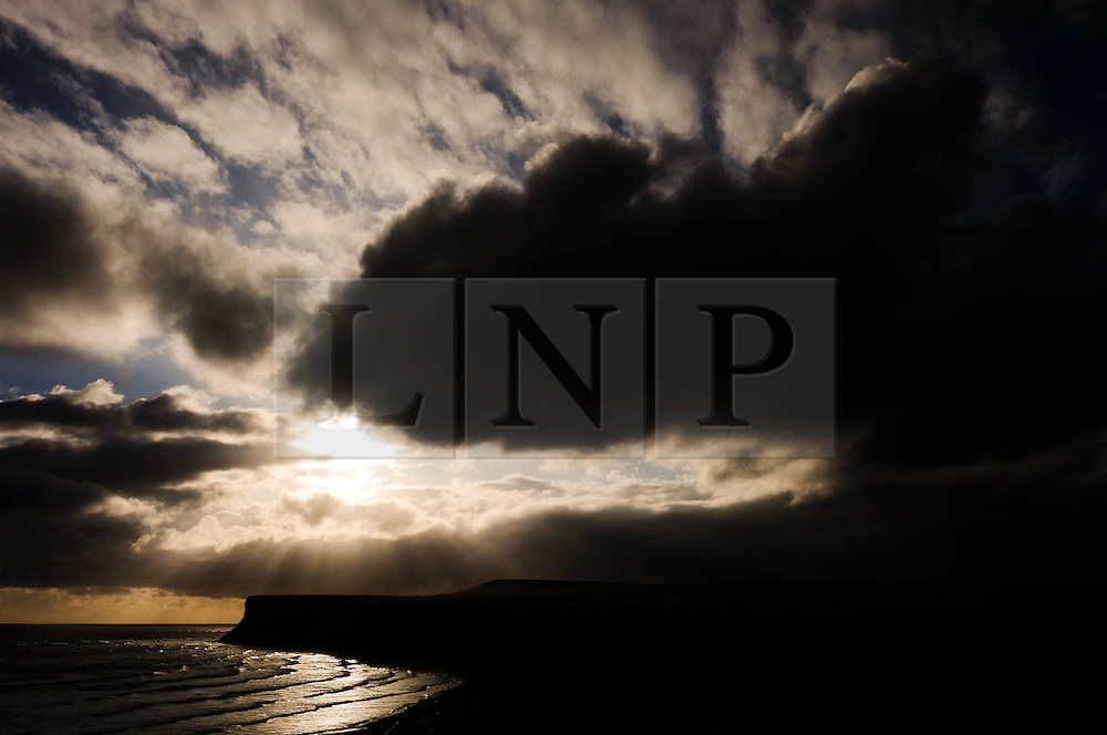 © Licensed to London News Pictures. 24/04/16<br /> Saltburn by the Sea, UK. <br /> <br /> Sunlight breaks through storm clouds over cliffs at Saltburn by the Sea. Temperatures dropped over the weekend as cold air blew down from the arctic.   <br /> <br /> Photo credit : Ian Forsyth/LNP